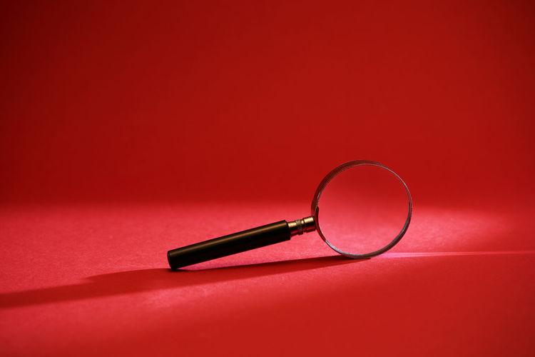High angle view of eyeglasses on table against red background