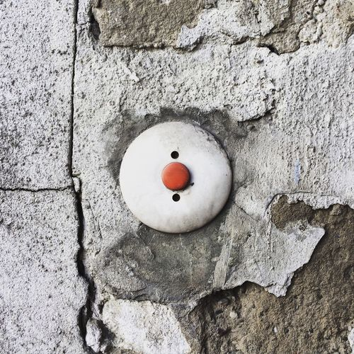 Close-Up Of Red Push Button On Damaged Wall