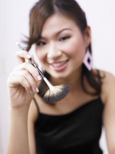 Portrait Of Smiling Woman Holding Make-Up Brush At Home