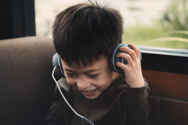 Cute smiling boy listening music on headphones at home
