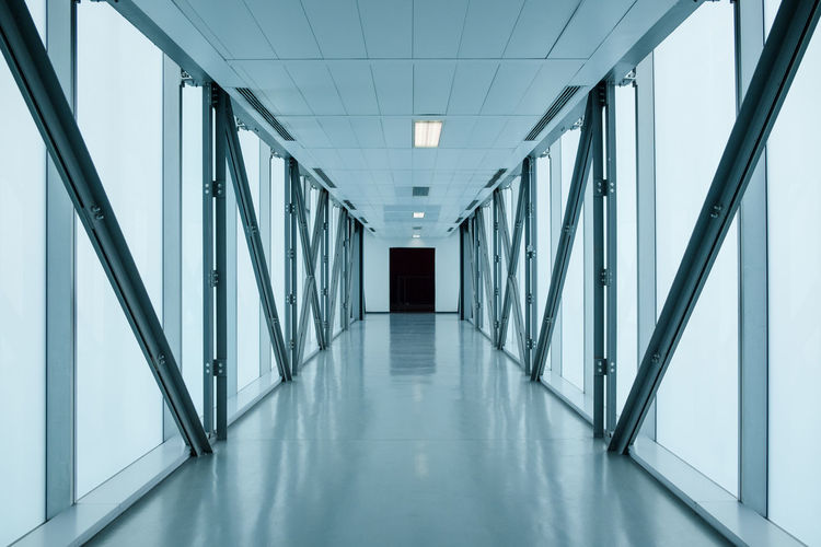 empty long corridor in modern building, might be an office, public building, exhibition grounds or an airport. Blue Color EyeEmNewHere Hallway Hospital Modern Airport Architecture Building Buildings Built Structure Corridor Day Design Exhibition Indoors  No People The Way Forward