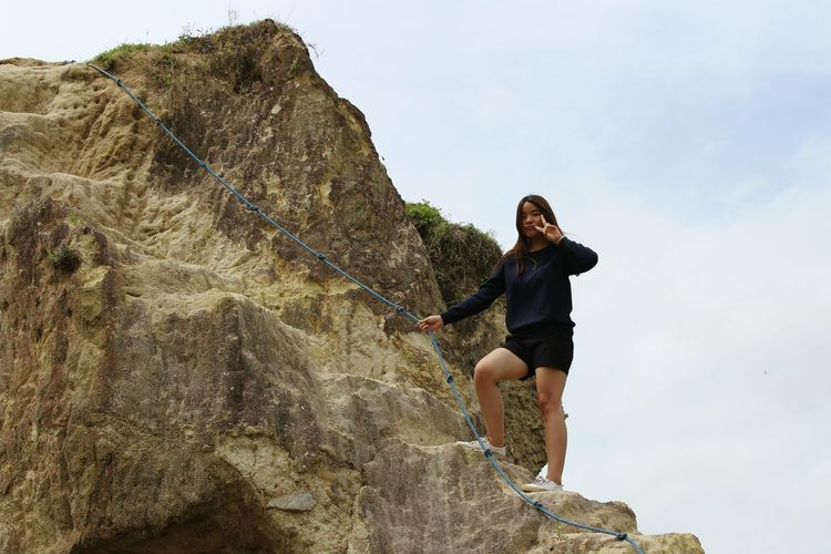 Low angle view of woman rock climbing against cloudy sky
