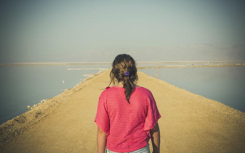 Rear view of girl in red top walking on walkway amidst sea against sky