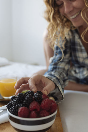 Midsection of woman with fruits on table