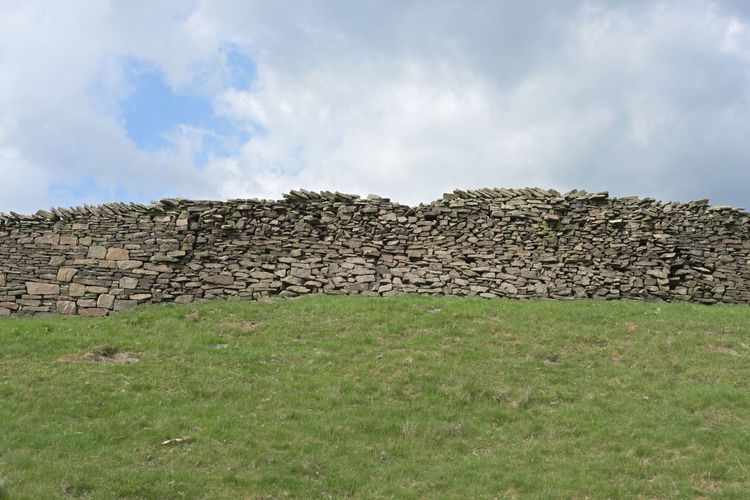 Stack of stone wall on field against sky