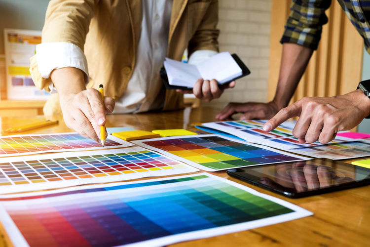 Midsection of design professionals working over color swatch on table