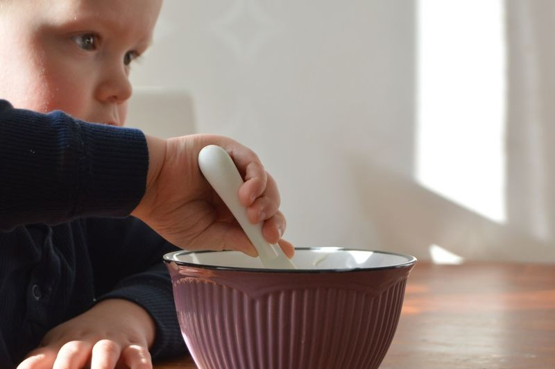 Close-up of boy with spoon in bowl on table at home
