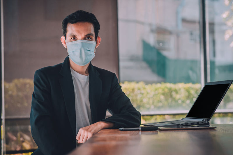 Portrait of businessman wearing mask sitting at office