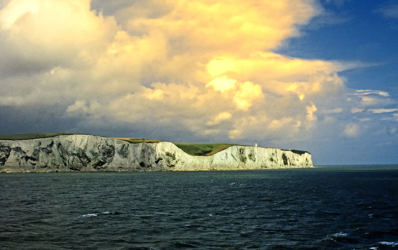 The White Cliffs of Dover - Dover, UK Architecture Sea Water Nature Sky Day Outdoors Tranquility Waterfront Scenics Beauty In Nature Lighthouses No People Tranquil Scene White Cliffs Of Dover Horizon Over Water Rock - Object Cloud - Sky Orange Sky Sunset The English Channel, Channel Port Perspectives On Nature