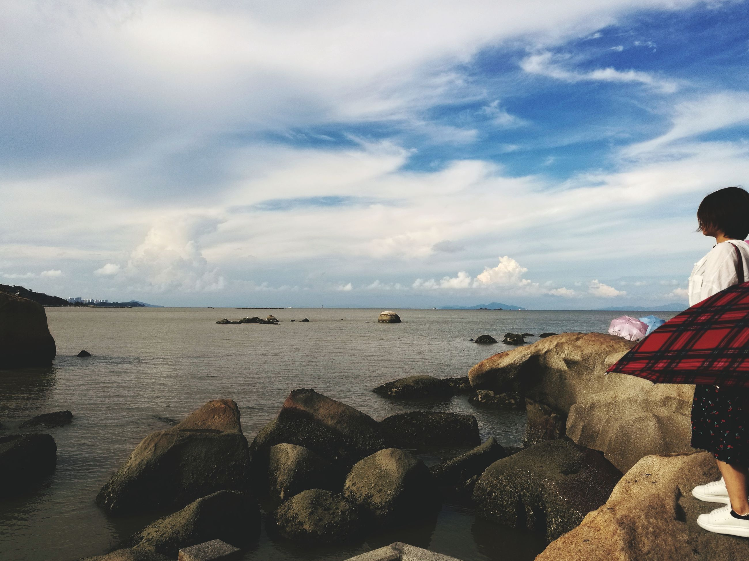 sea, water, sky, nature, rock - object, horizon over water, cloud - sky, scenics, tranquil scene, outdoors, tranquility, real people, day, sitting, beauty in nature, beach, vacations, standing, men, pebble beach, people