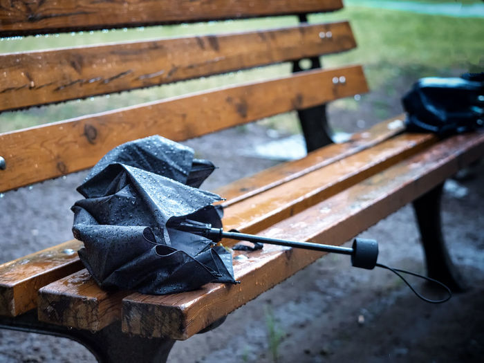 High angle view of wet umbrella on bench in park