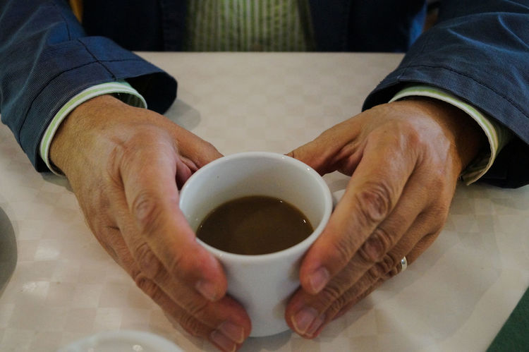 Adult Cafexperiment Close-up Coffee Cup Day Drink Food And Drink Holding Horizontal Human Body Part Indoors  Lifestyles Men One Man Only One Person Only Men People Person Refreshment Table Working