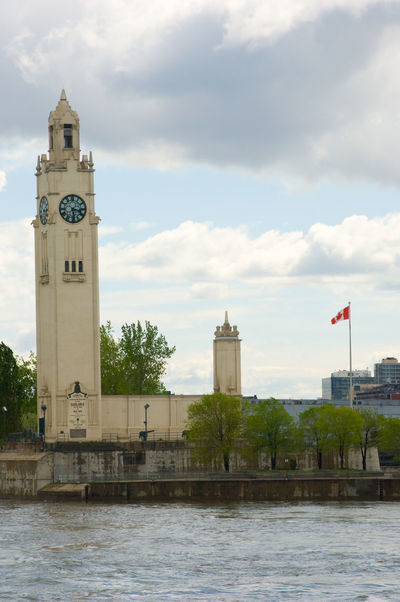 Montreal Clock Tower (also called the Sailor's Memorial Clock) in Old Port, Old Montreal, Quebec, Canada on a spring afternoon. Flag of Canada waving in the background. Architecture Built Structure City Clock Clock Face Clock Tower Clock Towers Cloud - Sky Day Flag Government Montreal, Canada Montréal No People Outdoors Politics Politics And Government Sailor's Memorial Clock Sky St Lawrence River Tower Travel Travel Destinations Tree Urban Skyline
