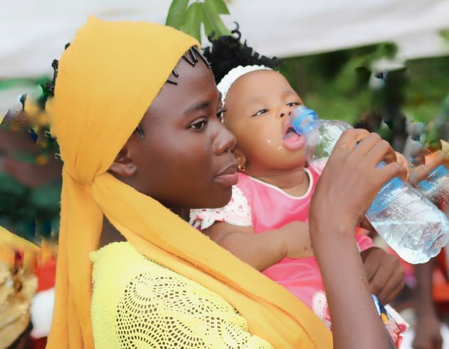 Side view of woman feeding water to daughter