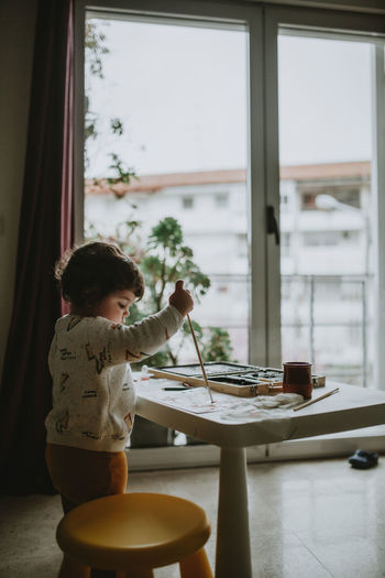 Side view of girl painting over paper on table at home