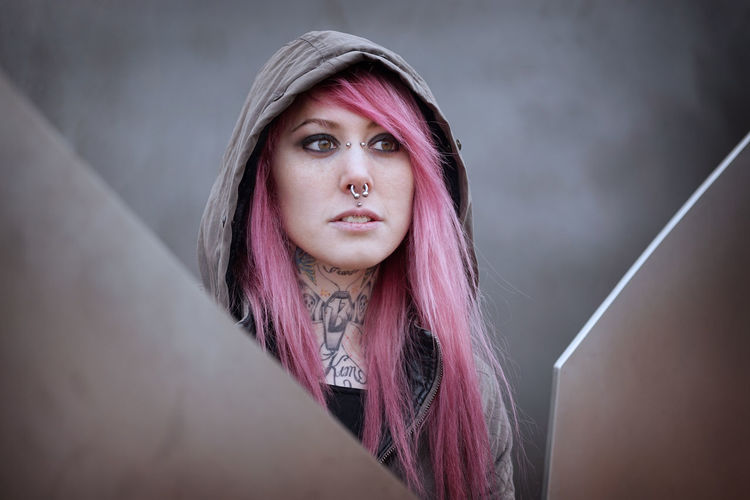 Young woman in pink hair looking away