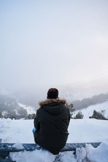 Rear view of man sitting on snow covered landscape against sky