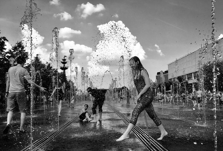 People on wet fountain against sky during rainy season