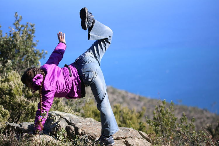 Woman exercising on rock against clear blue sky