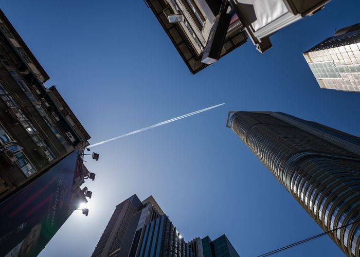 Directly below view of vapor trail over buildings in city