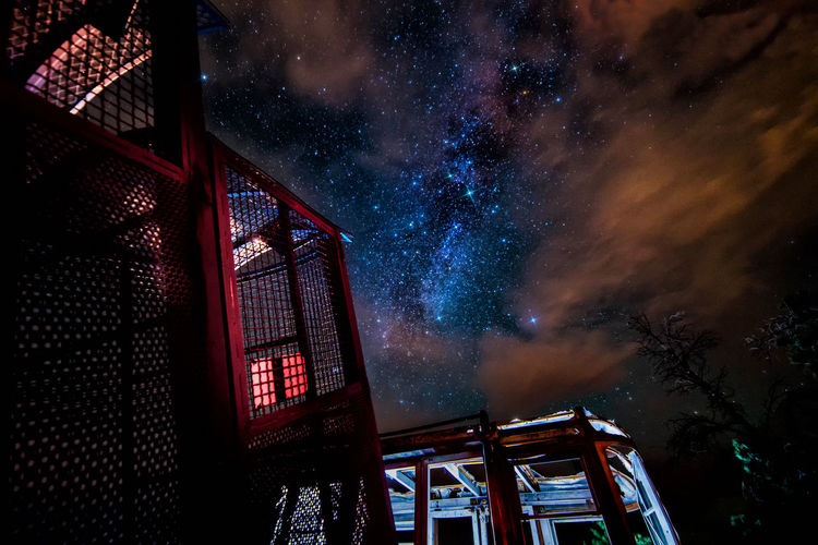 Old tramway and incline railway cars that were destroyed during a wildfire sit in a vacant lot, resting under the stars Car Dark Glowing Illuminated Lighting Equipment Low Angle View Milkyway Night Relics Sky Stars Starscape