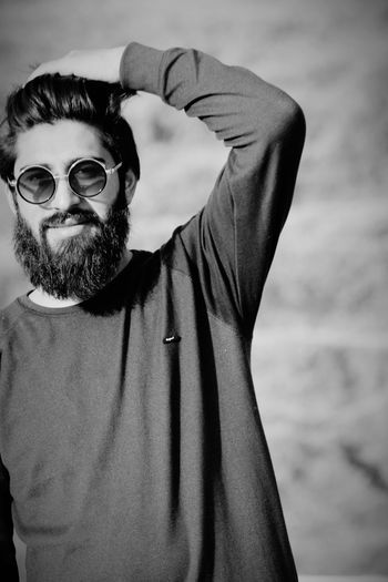 Portrait of bearded young man wearing sunglasses standing outdoors