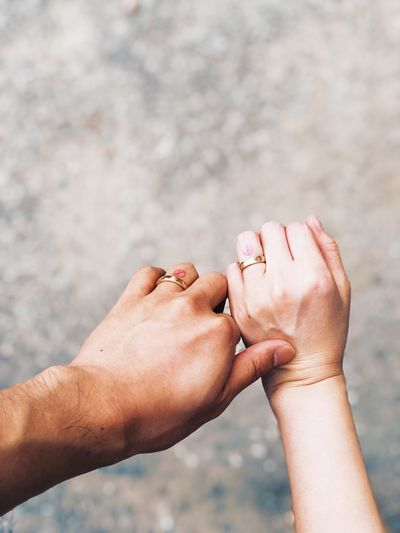 Cropped hands of couple wearing rings