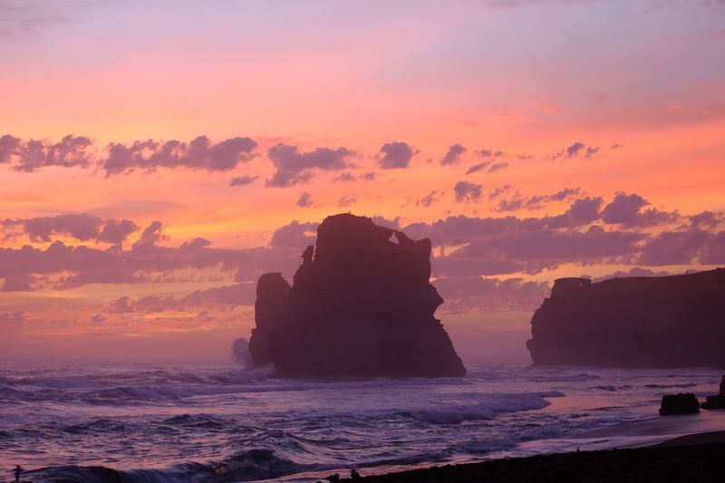 Silhouette rocks on shore against sky during sunset