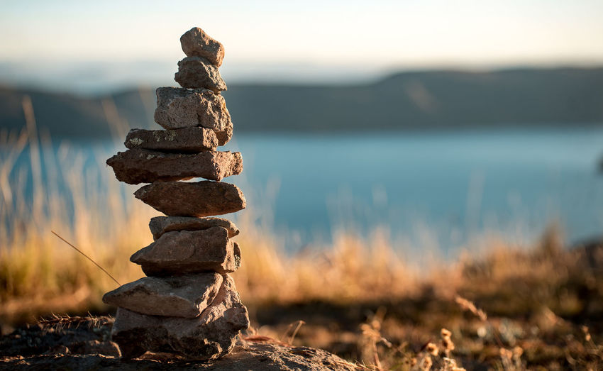 Stack Of Stones Against Lake During Sunset