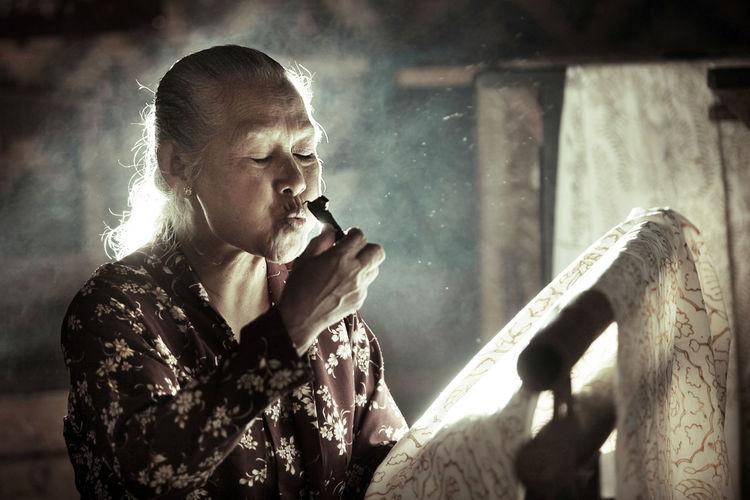 Side view of senior man holding cigarette