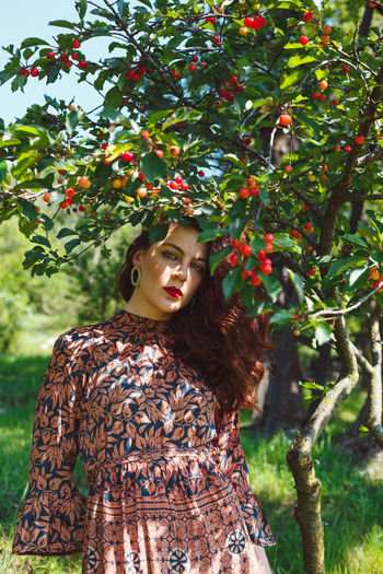 Woman standing by tree against plants