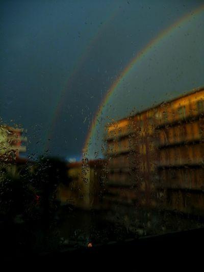 Rainbow over buildings seen through wet window