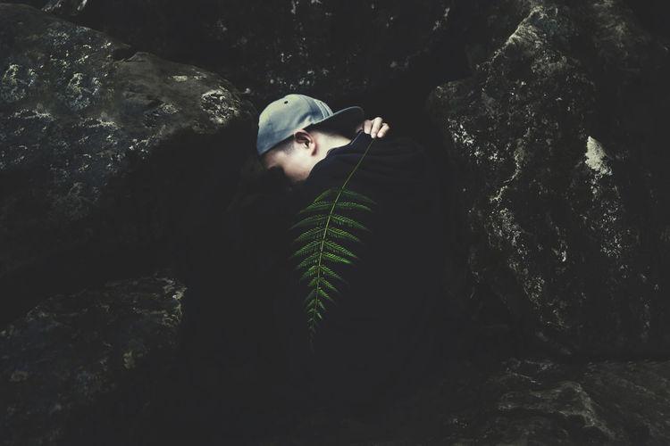 Man holding fern by rocks