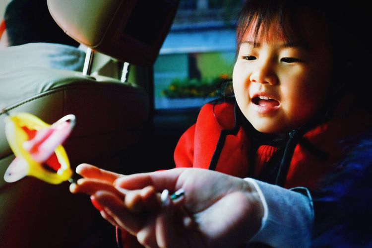 Cropped hand of woman holding toy by daughter traveling in car