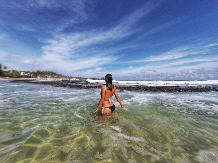 Rear view of woman wearing bikini while standing in sea against blue sky