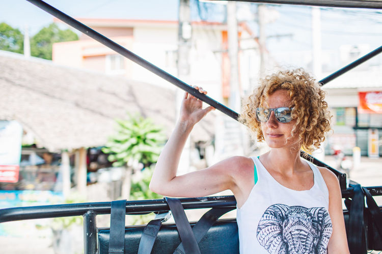 Curly Hair Girl Real People One Person Lifestyles Architecture Hair Hairstyle Glasses Front View Focus On Foreground Leisure Activity Women Portrait Built Structure Young Adult Day Females Waist Up Fashion