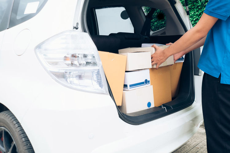 Midsection of man holding boxes in car