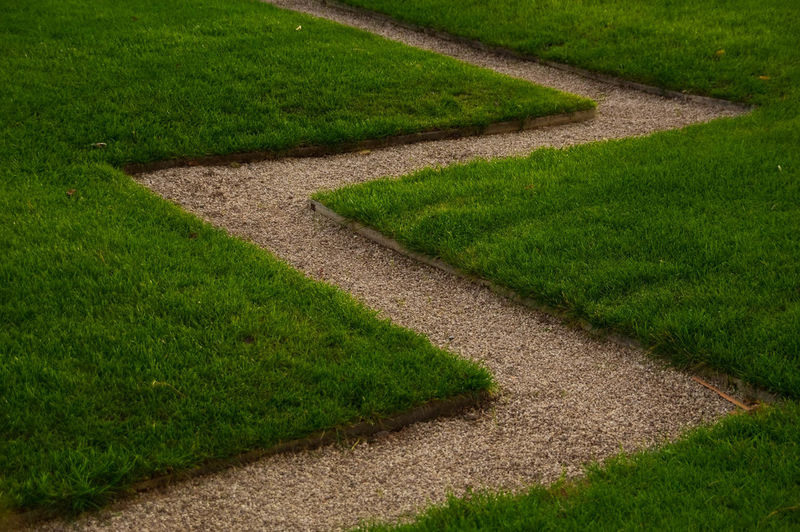 High angle view of garden path amidst grass in park