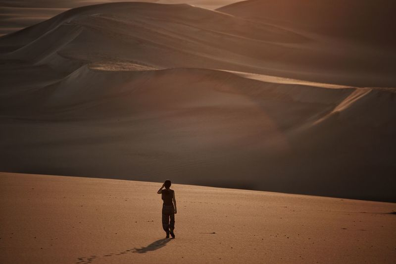 Full length of man standing on sand dune in desert