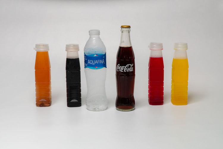 Close-up of bottles on shelf against white background