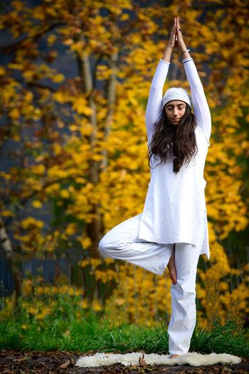 Full length of woman meditating against autumn tree