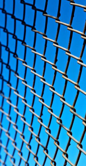 Full frame shot of metal fence against blue sky