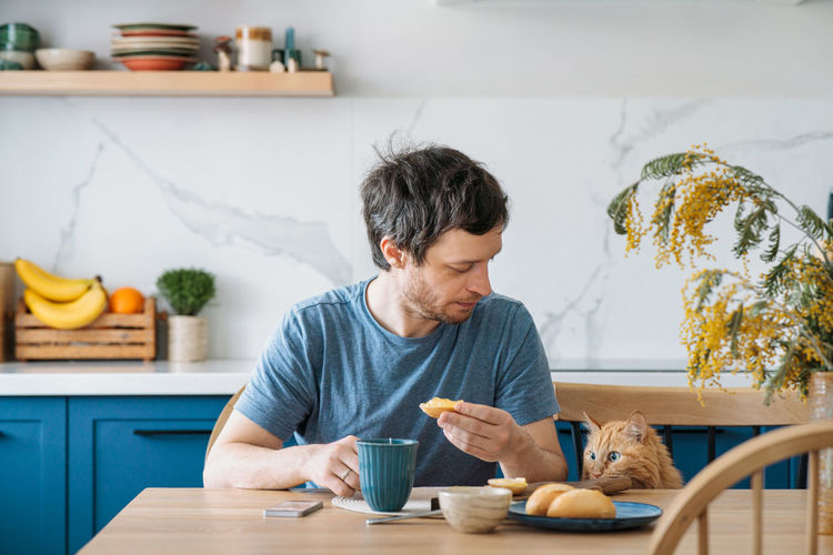 Man having food in kitchen