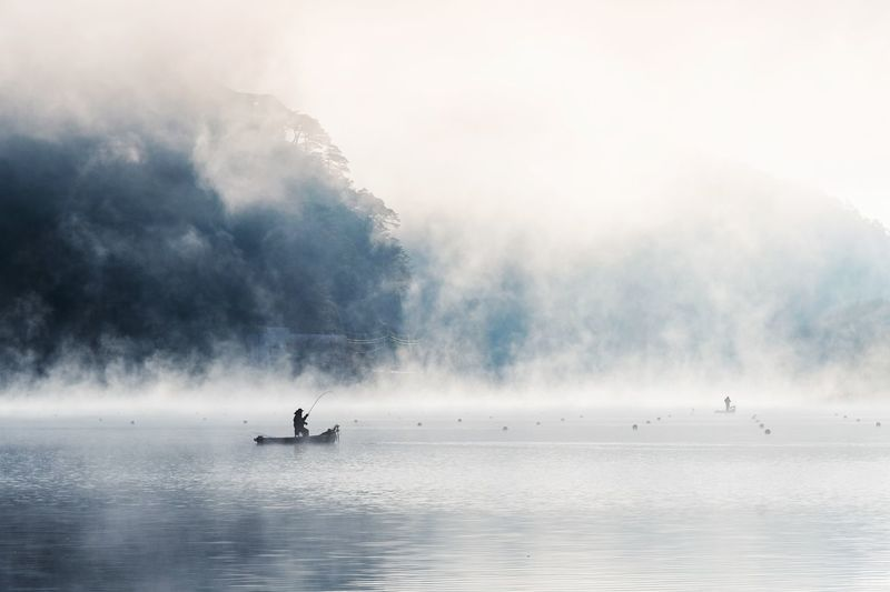 Silhouette Fisherman Fishing On Boat In Lake During Foggy Weather