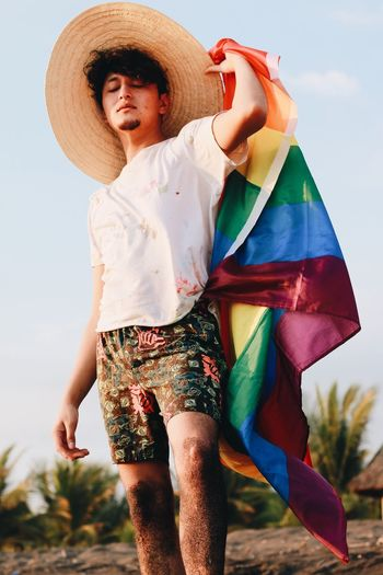 Young man holding rainbow flag while standing at beach