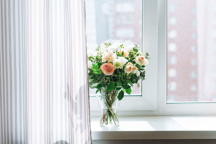 Bouquet of white and pink roses, greens and other flowers on window sill at home