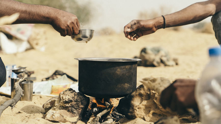 Cropped Hands Of Hikers Making Tea At Jaisalmer Desert