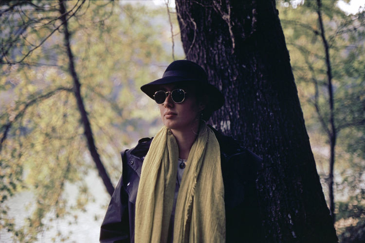 Woman wearing sunglasses standing against tree trunk in forest