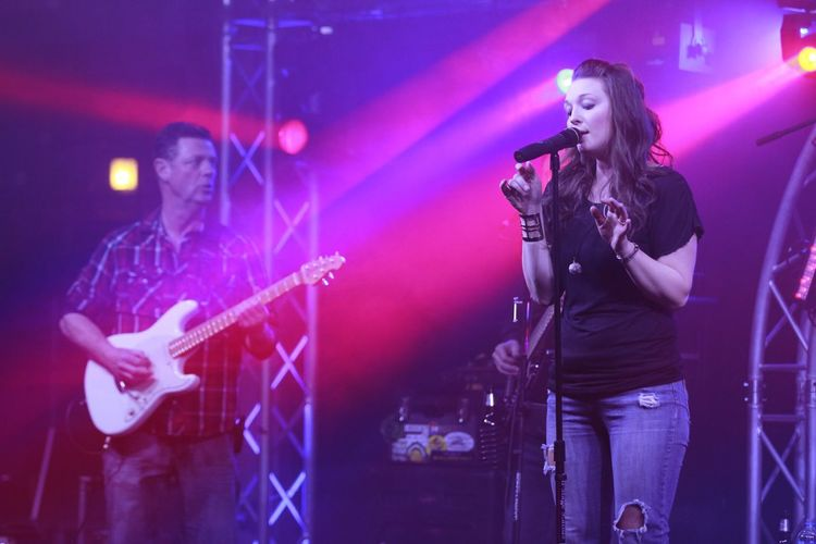 Woman Singing While Man Playing Guitar On Stage