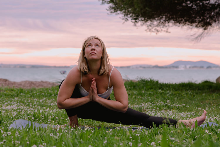 Young blonde woman practicing yoga outdoors at sunset on a grass field with wild flowers and the sea and mountains as background. Alcanada beach, Mallorca, Balearic Islands, Spain. Yoga Yoga Pose Woman Portrait Woman Doing Yoga Yogini Outdoor Yoga Wild Flowers Green Grass Pine Tree Tree Sunset Sunset Colors Sea Background Mountain Background Yoga At The Beach Sunset Yoga Yoga Outdoor Young Woman Green Pink Background Pink Clouds Pink Clouds At Sunset Relaxation Relaxing Time Blond Hair Blonde Hair Short Hair 30-35 Years Old One Person Lifestyles Real People Leisure Activity Beauty In Nature Sky Nature Front View Grass Outdoors Beautiful Woman Contemplation Yoga On The Beach Yoga On The Grass Spring Flowers Field Tranquillity Tranquility Zen Healthy Lifestyle Exercise Yoga Practice